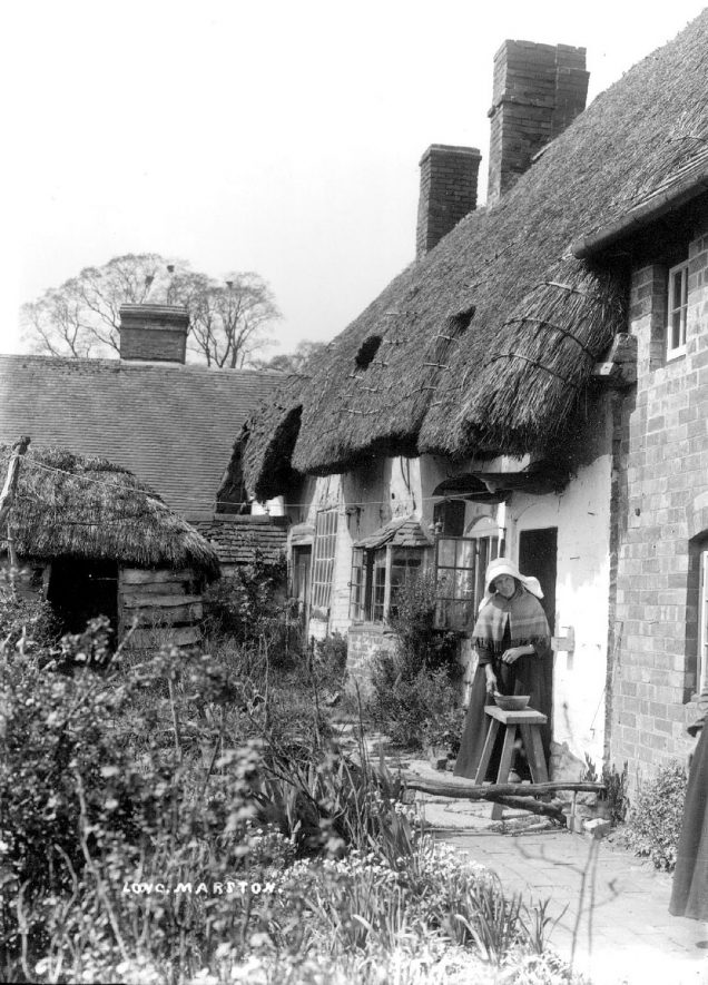 Woman standing outside old thatched cottages, Long Marston.  1900s |  IMAGE LOCATION: (Warwickshire County Record Office)