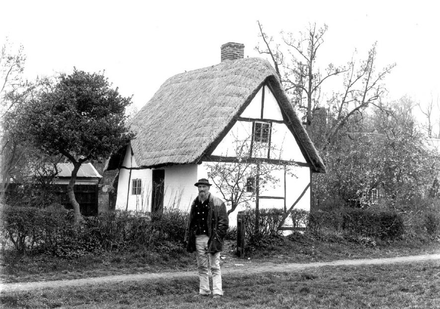 Old timber framed, thatched cottage with man outside.  Welford on Avon.  1900s |  IMAGE LOCATION: (Warwickshire County Record Office)