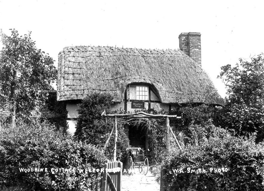 Timber framed, thatched cottage with bath chair outside known as Woodbine Cottage, Welford on Avon.  1900s |  IMAGE LOCATION: (Warwickshire County Record Office)