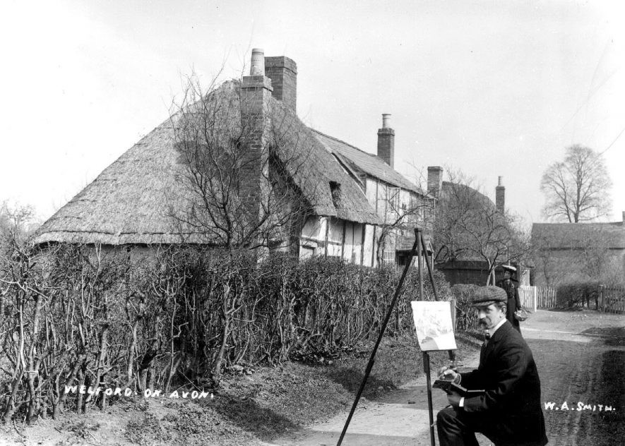 Artist painting a picture of old cottages in Welford on Avon.  1900s |  IMAGE LOCATION: (Warwickshire County Record Office)