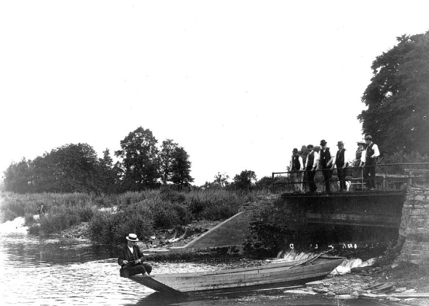 Man in a punt beside the weir on the River Avon at Welford on Avon.  1900s |  IMAGE LOCATION: (Warwickshire County Record Office)