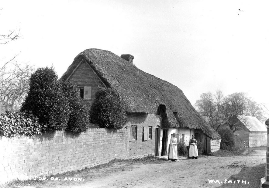 Old thatched cottages with two women standing in front in Weston-on-Avon.  1900s |  IMAGE LOCATION: (Warwickshire County Record Office)
