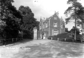 The Lodge at Hatton Asylum with a nurse standing at the gate.  1900s |  IMAGE LOCATION: (Warwickshire County Record Office)