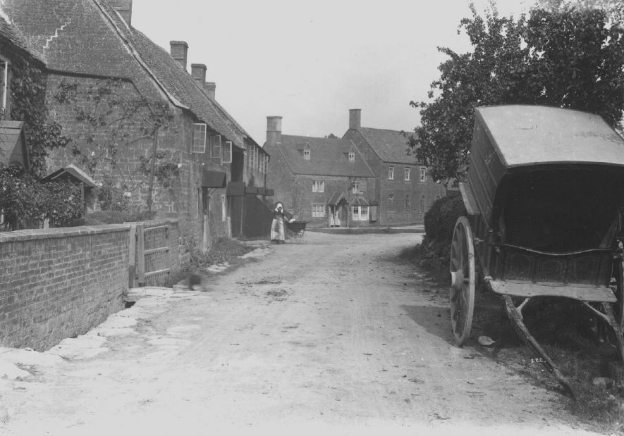 Part of village street, Ilmington, showing cottages, woman with pram, delivery cart (no horse).  1900s |  IMAGE LOCATION: (Warwickshire County Record Office)