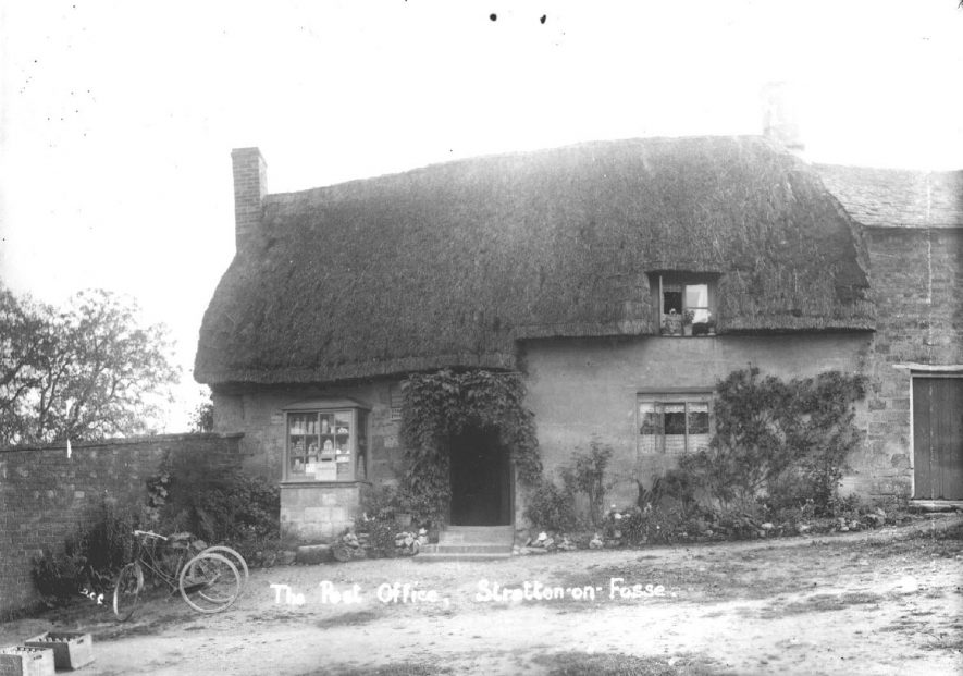 Stretton on Fosse post office, part of thatched cottage. Tricycle outside.  1900s |  IMAGE LOCATION: (Warwickshire County Record Office)