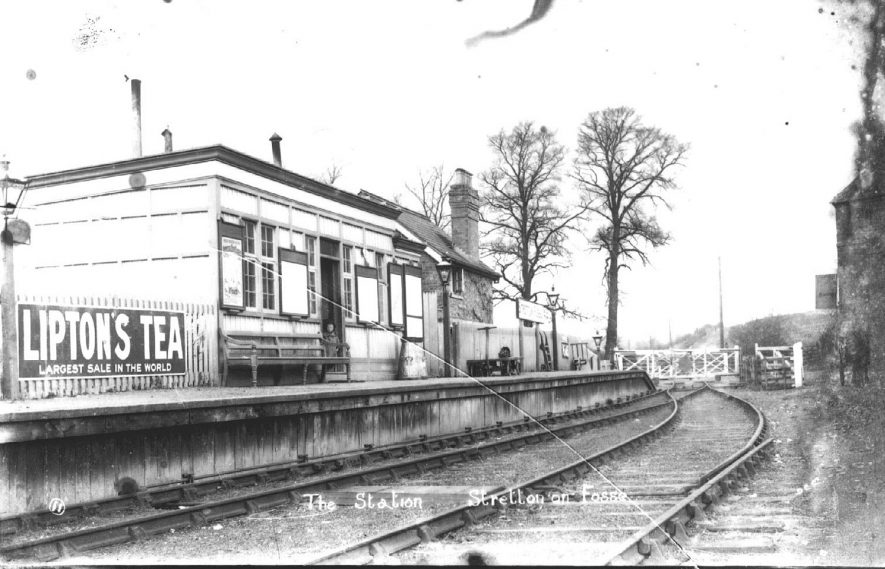 Stretton on Fosse railway station.  Advertisement board and level crossing gates.  1900s |  IMAGE LOCATION: (Warwickshire County Record Office)