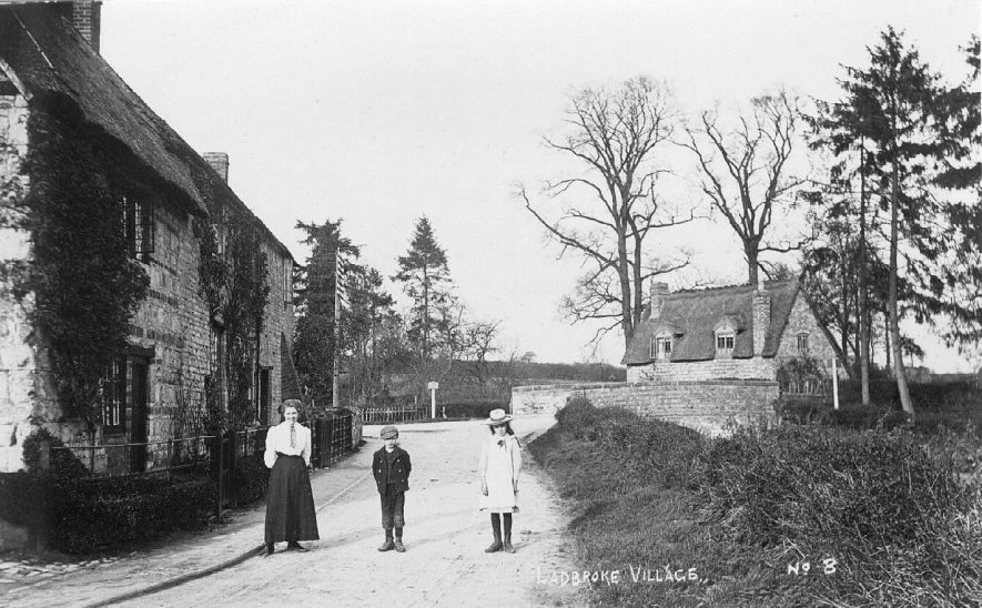 Leamington street with a woman and two children standing in the road. 1900s[This is Bridge Street, Ladbroke, close to, and looking towards, its T-junction with Banbury Road. The distinctively stripy brick/stonework on the house on the left of the picture and the slight shift in roof lines to adjoining house can still be identified on Google Street View. The stone bridge parapet has been replaced by a green painted metal railing.] |  IMAGE LOCATION: (Warwickshire County Record Office)