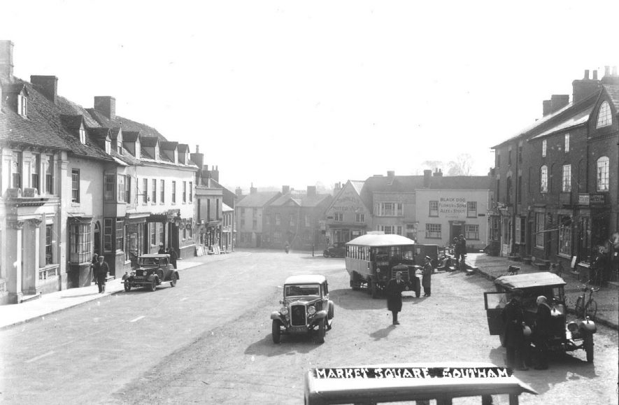 Market Hill, Southam showing the Black Dog and the Craven Arms including buses and motor cars parked in the road.  1920s |  IMAGE LOCATION: (Warwickshire County Record Office)