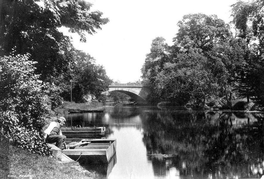 Bridge leading over River Avon from Banbury Road, Warwick. Man with flat boat at side of river.  1890s |  IMAGE LOCATION: (Warwickshire County Record Office)
