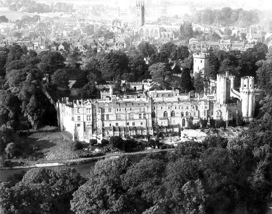 Aerial view of Warwick castle and town, showing St Mary's Church and old county goal in distance, beyond gas holder.  1930s |  IMAGE LOCATION: (Warwickshire County Record Office)