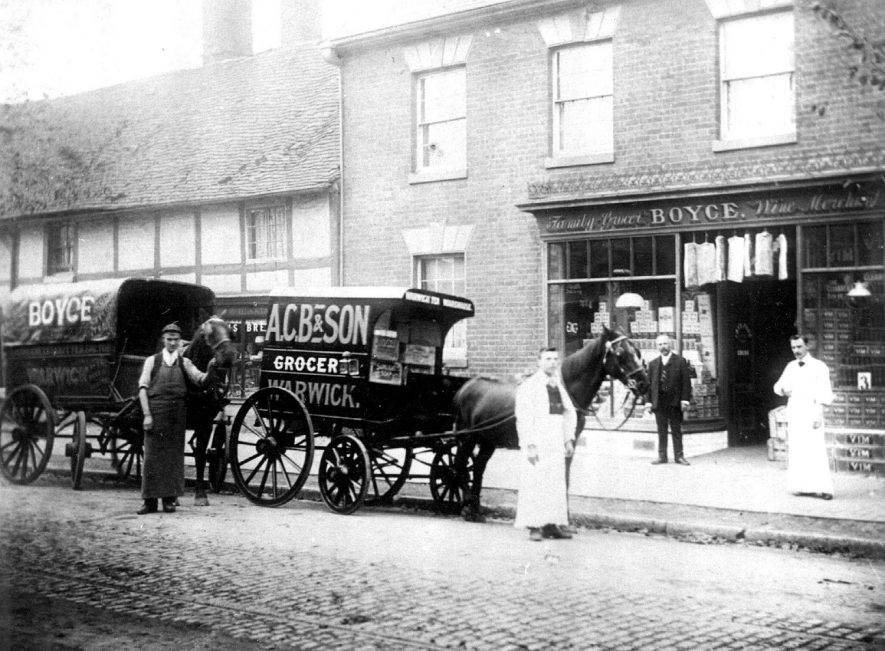 Coton End, Warwick. Boyce's grocery shop and two horse-drawn delivery vehicles. Four men, two in white aprons, one in sacking apron posing outside shop.  1900s |  IMAGE LOCATION: (Warwickshire County Record Office)