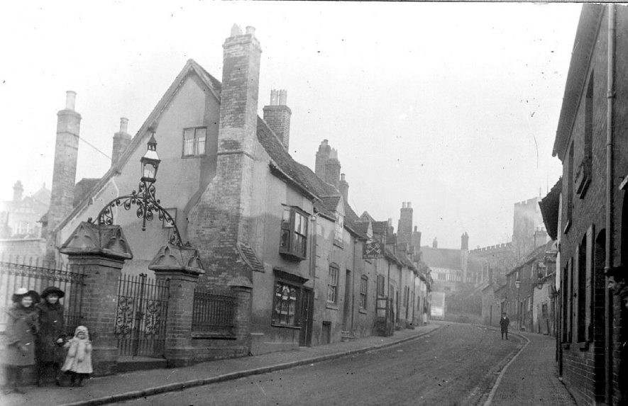 Friars Street, looking toward the West Gate, Warwick.  Parish Room railings and gateway with three children standing by.  1900s |  IMAGE LOCATION: (Warwickshire County Record Office)