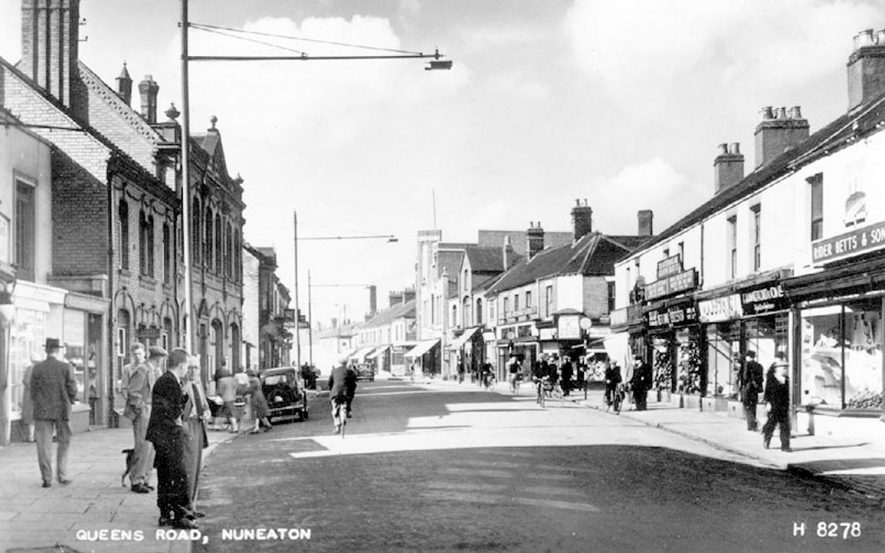 Shops, motor car and street lighting on Queen's Road, Nuneaton.  1950s |  IMAGE LOCATION: (Warwickshire County Record Office)