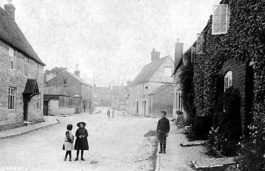 Mill Street leading into High Street, Harbury. The Dog Inn is in the background and children are playing in the foreground. The second shop on the left in High Street is supposedly the oldest rural Co-op shop.  1920s |  IMAGE LOCATION: (Warwickshire County Record Office)