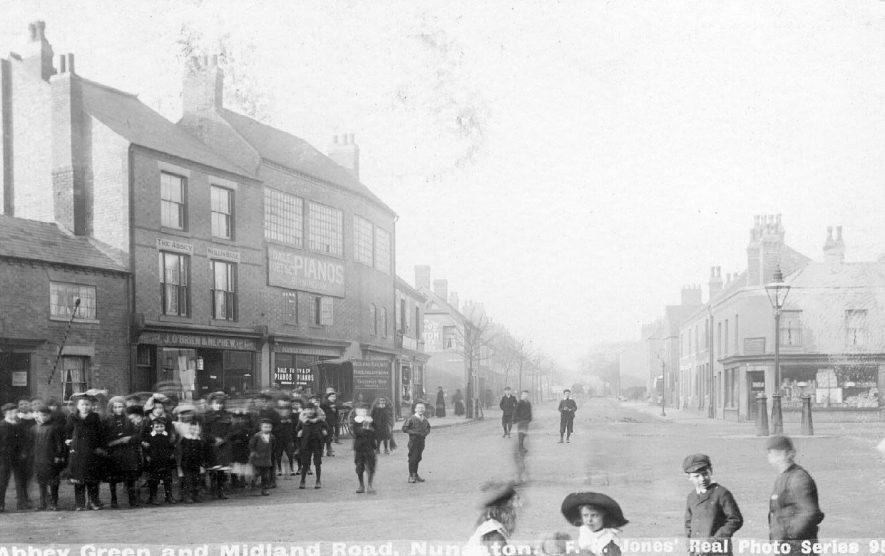 Group of children standing in front of shops in Abbey Green and Midland Road, Nuneaton.  1900s |  IMAGE LOCATION: (Warwickshire County Record Office)