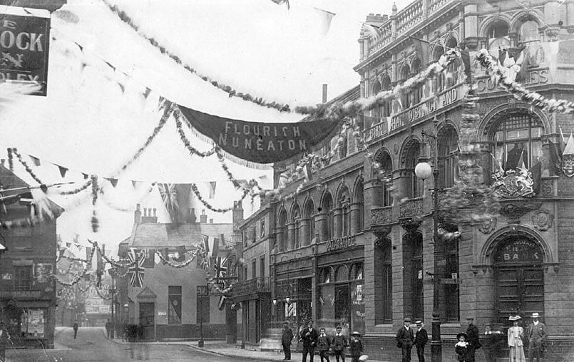 Nuneaton Market Place decorated with banner, Union Jacks and bunting. People on pavement, possibly waiting for parade.  1900s |  IMAGE LOCATION: (Warwickshire County Record Office)