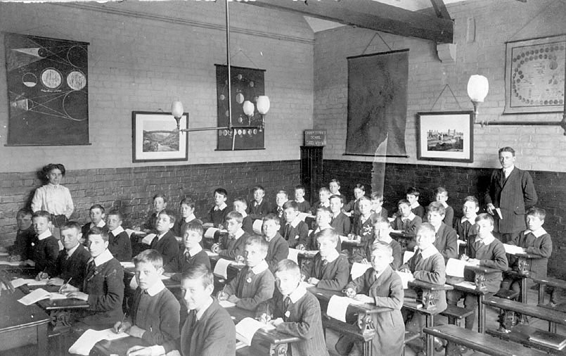 Interior of classroom at Abbey Street School, Nuneaton, showing boys at desks and teachers, one man, one woman.  1900s |  IMAGE LOCATION: (Warwickshire County Record Office)