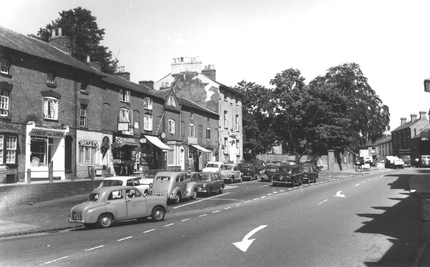 Market Hill, Southam showing shops on the left including Parker & Lines; motorcars parked in the street.  1960s |  IMAGE LOCATION: (Warwickshire County Record Office)