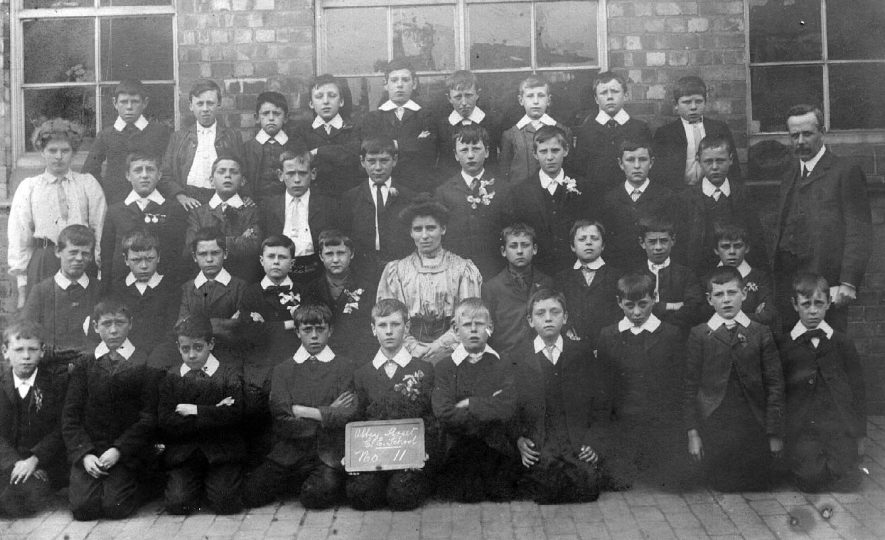Group photograph of class of boys at Abbey Street School, Nuneaton. One male, one female teacher and one pupil teacher. Some of the boys are wearing attendance medals.  1900s. |  IMAGE LOCATION: (Warwickshire County Record Office)
