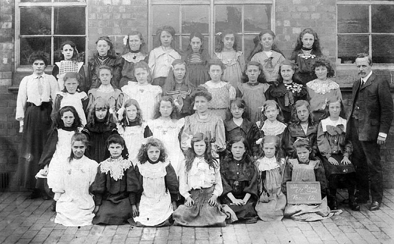 Group photograph of Abbey Street School girls, Nuneaton. One male, two female teachers. Two girls wearing attendance medals.  1900s |  IMAGE LOCATION: (Warwickshire County Record Office)