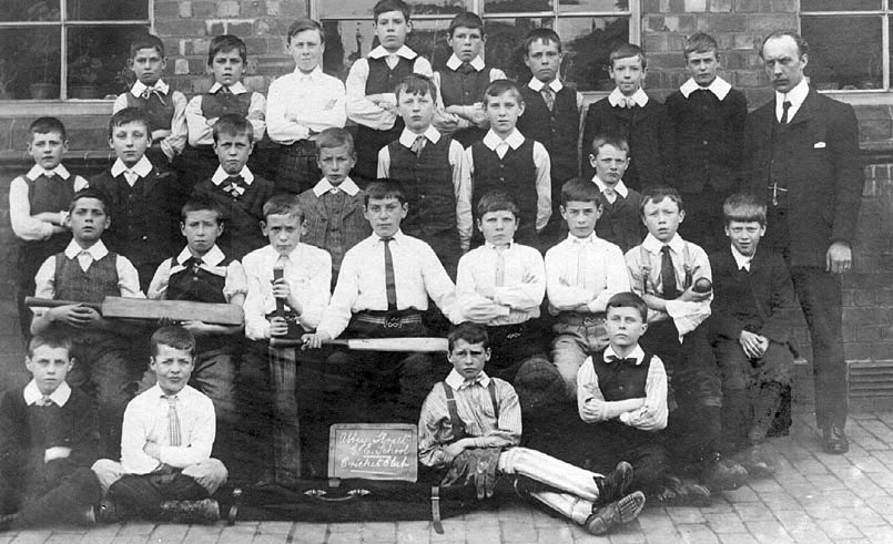 Group photograph of boys at Abbey Street School Cricket Club, Nuneaton, with one male teacher. Three boys with cricket bats, one with ball and one wearing pads.  1900s |  IMAGE LOCATION: (Warwickshire County Record Office)