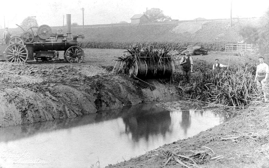 Fowler ploughing engine [of about 1880] and stream dredging machinery in operation, Nuneaton. The ploughing engine, or wrought iron engine as it was commonly called, was always used in pairs; there would be another one on the other side of the dredger.  1900s |  IMAGE LOCATION: (Warwickshire County Record Office)