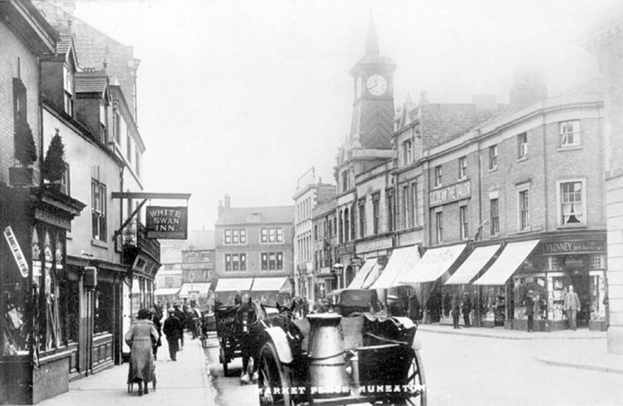 Nuneaton, Market Place, showing shops, pedestrians and horse-drawn vehicles, including milk cart with churn.  1920s |  IMAGE LOCATION: (Warwickshire County Record Office)