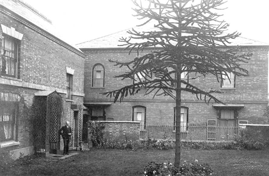 The Old Meeting Chapel, Bedworth.  Built 1726, the roof raised in 1808. On left is the Manse (demolished in late 1950s) showing a Monkey Puzzle ( Aracauria) tree. Minister in the doorway of the Manse.  1900s |  IMAGE LOCATION: (Warwickshire County Record Office)