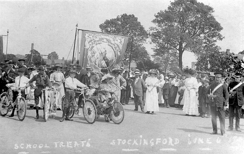Sunday School Treat in Stockingford. Gathering of people in various types of dress and uniform and carrying an ornate banner.  1900s |  IMAGE LOCATION: (Warwickshire County Record Office)