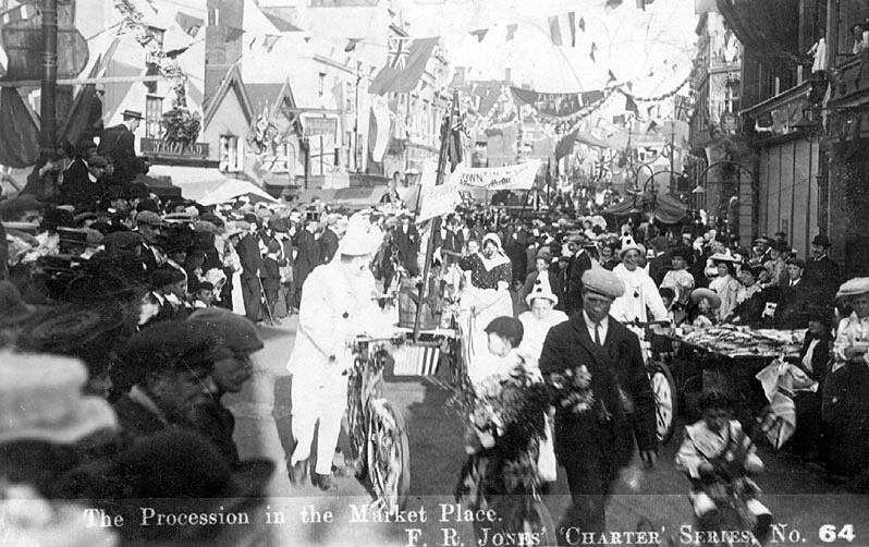 A procession (event unknown) with people in fancy dress, passing through the Market Place, Nuneaton.  1907    IMAGE LOCATION: (Warwickshire County Record Office)