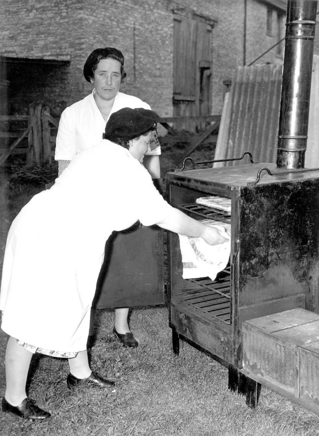 Emergency feeding exercise at Halford showing Mrs. L.N. Horne taking a tray of apple tarts from the oven of a No.4 field cooker, watched by Mrs. R .Smith.  September 25th 1956 |  IMAGE LOCATION: (Warwickshire County Record Office) PEOPLE IN PHOTO: Smith, Mrs R, Smith as a surname, Horne, Mrs L N, Horne as a surname