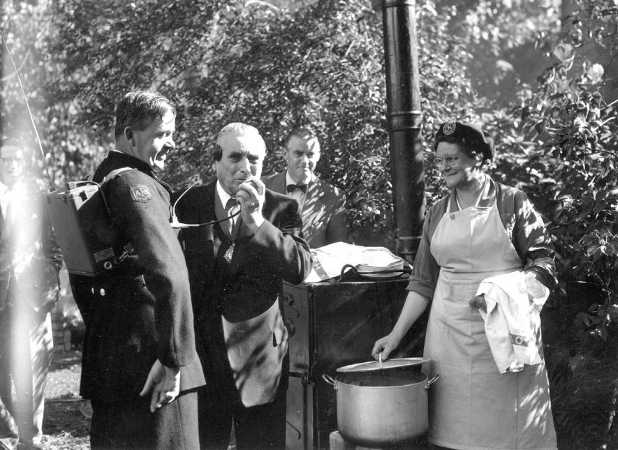 The Mayor of Rugby, Alderman S.G. Gibson, using a walkie talkie to report how the meal is being cooked by members of the Welfare Section on emergency cooking stoves. Also in the photograph, to the left, is Fireman D.J. Newman. At the cooker is Mrs. C. Rhead, one of the cooks, and background centre, Mr T.L. Duffy, Town Clerk.  September 24th 1955 |  IMAGE LOCATION: (Warwickshire County Record Office) PEOPLE IN PHOTO: Rhead, Mrs C, Rhead as a surname, Newman, D J, Newman as a surname, Gibson, Ald S G, Gibson as a surname, Duffy, Mr T L, Duffy as a surname
