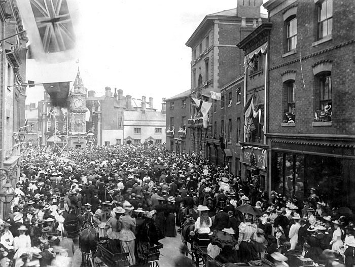 Large gathering of people celebrating an event, almost certainly the Golden Jubilee of Queen Victoria, 1837-1897, in The Market Place, Rugby.  1897 |  IMAGE LOCATION: (Warwickshire County Record Office)