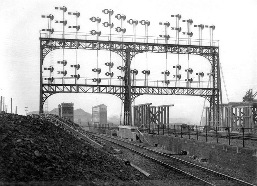Large railway signal gantry at the old station, Rugby,  after it had been duplicated with sky arms in the late 1890s in readiness for the viaduct for new Great Central Railway London Extension.  1890s [It has been suggested that the whole gantry was built at the same time in readiness for the GCR girder bridge which would have blocked the view of the original signals.][The gantry was built as one unit and incidently was paid for by the GCR.] |  IMAGE LOCATION: (Warwickshire County Record Office)