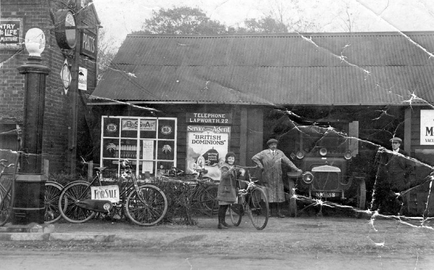 Daimler - 25hp, in garage entrance at Lapworth. This car was registered to Cheshire Garage, Stratford Road, Hockley Heath in 1921. Picture also shows a selection of bicycles and a garage worker.  1920s |  IMAGE LOCATION: (Warwickshire County Record Office)