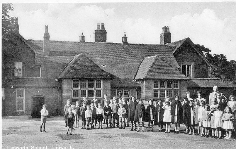 Pupils and staff outside the school at Lapworth.  1930s  [It is believed that the Head Teacher is Mr Belton. The girls capes are red in colour and originally were supplied by benefactor, Mr Melson.] |  IMAGE LOCATION: (Warwickshire County Record Office)