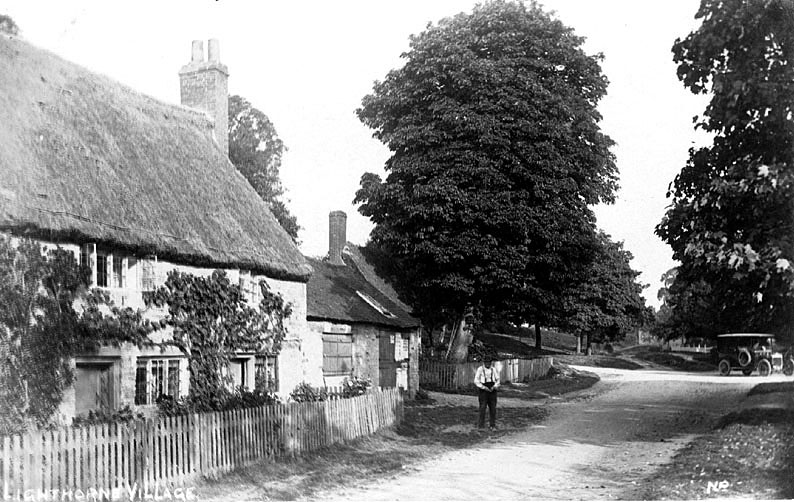 Thatched cottage with smithy and forge attached, looking along Old School Lane in Lighthorne.  1900s |  IMAGE LOCATION: (Warwickshire County Record Office)