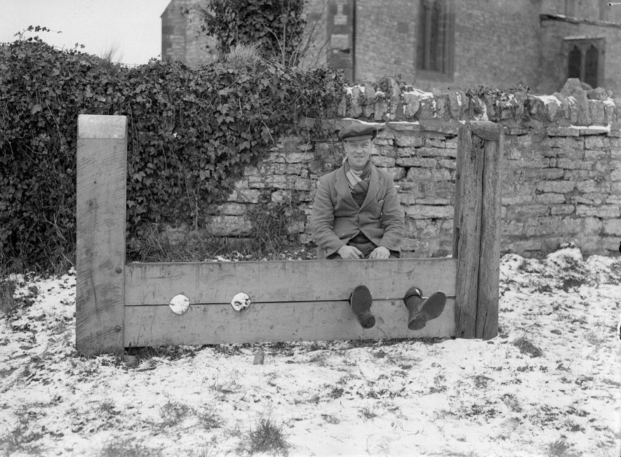 Ufton stocks with man in the stocks, outside the Church.  1938 |  IMAGE LOCATION: (Warwickshire County Record Office)