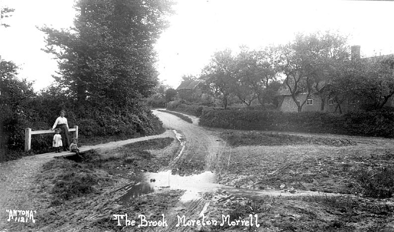 Woman and two children standing on small bridge over the brook at Moreton Morrell.  1900s |  IMAGE LOCATION: (Warwickshire County Record Office)