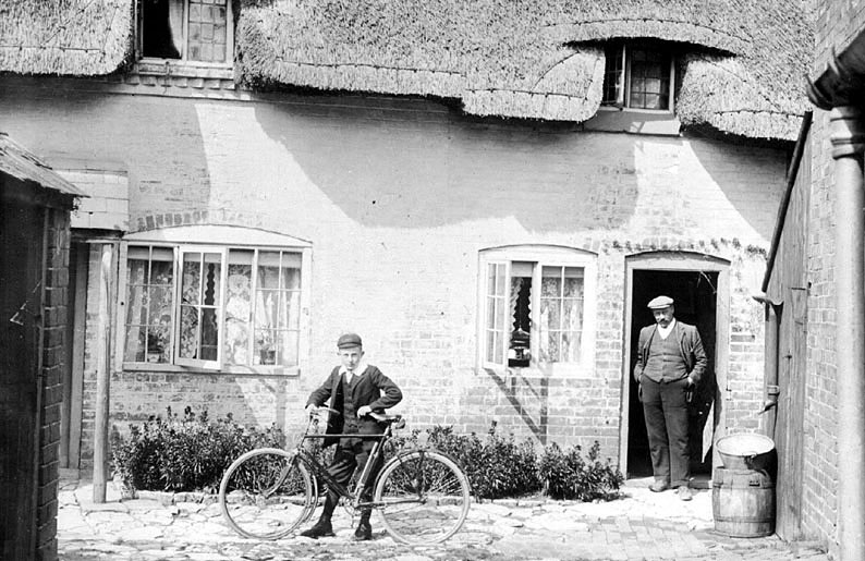 Man and boy with a bicycle standing outside a thatched cottage in Moreton Morrell.  1900s |  IMAGE LOCATION: (Warwickshire County Record Office)