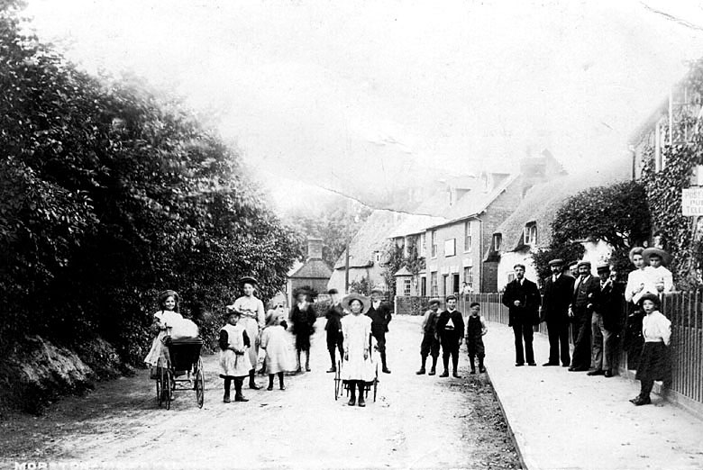 Group of children and adults standing outside the post office in Moreton Morrell.  1900s |  IMAGE LOCATION: (Warwickshire County Record Office)