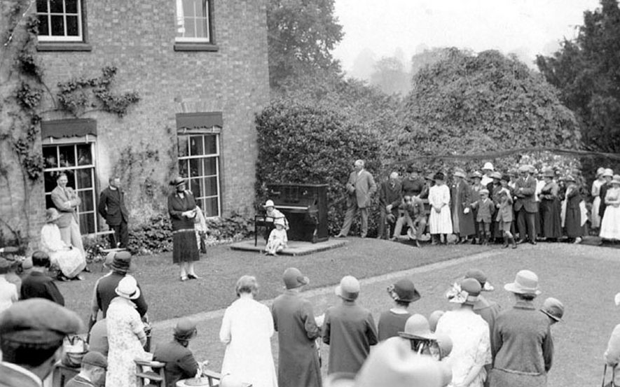 Lady addressing a social gathering in the garden of a large house at Long Lawford.  1920s |  IMAGE LOCATION: (Warwickshire County Record Office)