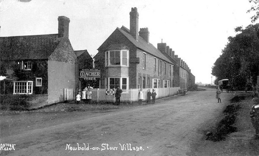 Village scene at Newbold on Stour.  The advertisement over the yard entrance reads: North British Clincher Tyres, and on the fencing: Mex motor spirit.  There is a motor cycle and sidecar  in the middle distance, parked against the fencing. |  IMAGE LOCATION: (Warwickshire County Record Office)