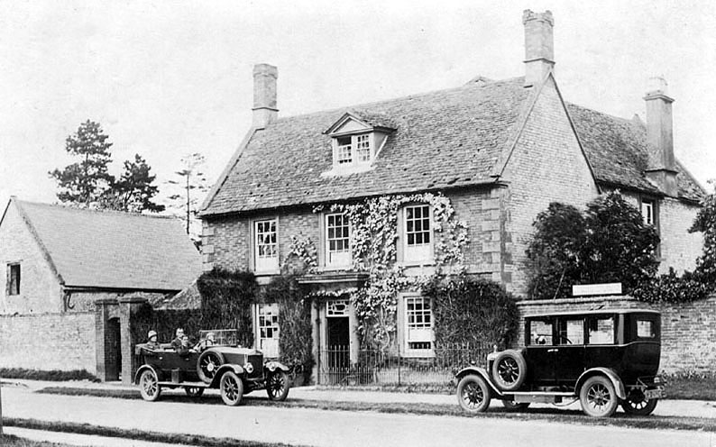 Two old motor cars, one tourer, standing in front of a big house in Newbold on Stour.  1920s |  IMAGE LOCATION: (Warwickshire County Record Office)