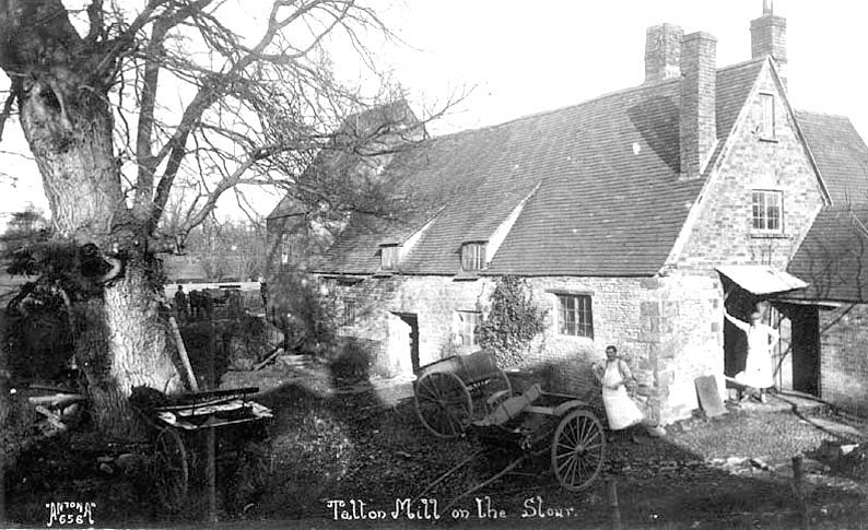 Talton Mill on the River Stour with two workers and various carts outside, Newbold-on-Stour.  1920s.[The mill was operated by a Mr.Budden from 1941.He and his family lived in a detached house overlooking the mill.The owners, the