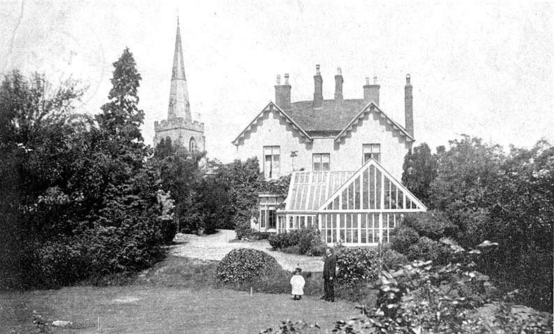 Newton Regis church and vicarage with a child in the vicarage garden.  1910s |  IMAGE LOCATION: (Warwickshire County Record Office)