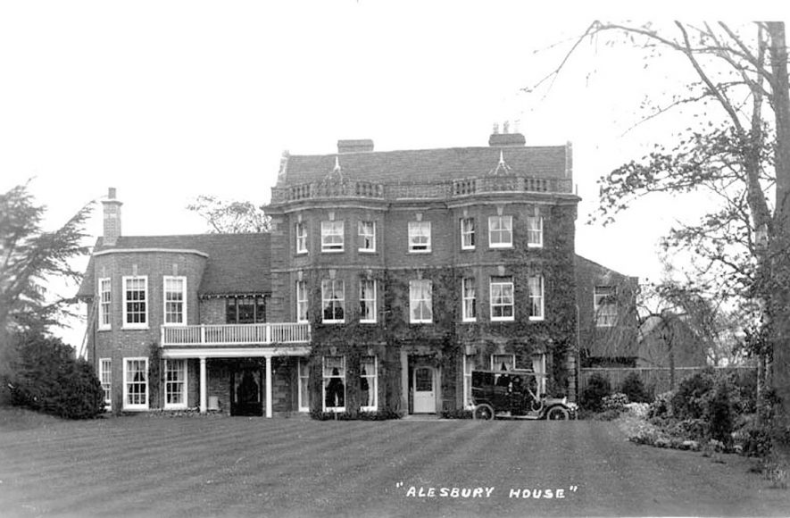 Aylesbury House front elevation, showing part of gardens and a motor car, Packwood.  1910s |  IMAGE LOCATION: (Warwickshire County Record Office)