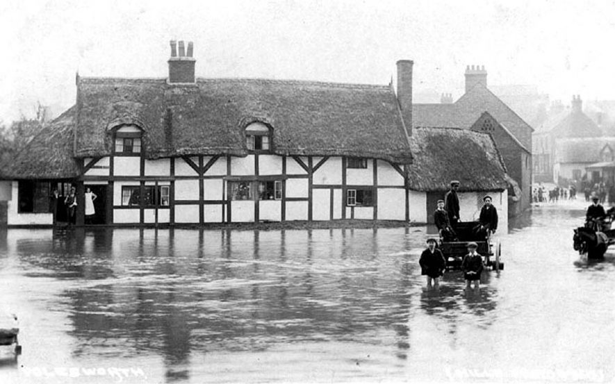 Part of Polesworth during a flood. Timbered and thatched cottages and people wading in water.  1900s |  IMAGE LOCATION: (Warwickshire County Record Office)