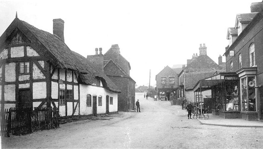 Market Street, Polesworth, showing thatched and timbered cottages and shops.  1900s |  IMAGE LOCATION: (Warwickshire County Record Office)