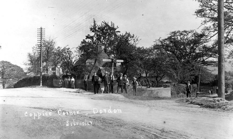 Group of people standing at the cross roads at Coppice Corner.  On the right of the picture there is a large steel cable supporting the telegraph pole.  1900s |  IMAGE LOCATION: (Warwickshire County Record Office)
